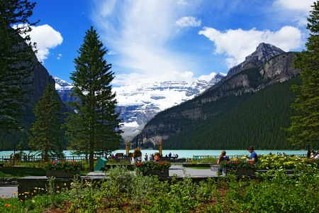 people chilling out and dating in front of lake louise, seen from the Fairmont Chateau Lake Louise hotel