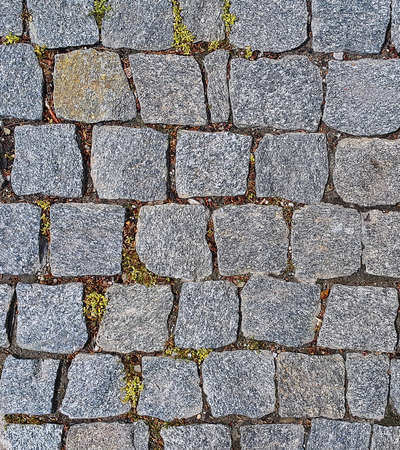 Stone pavement texture. Granite cobble stoned pavement background. Stone background of pavement with rough granite boulders with little bit grass and moss.