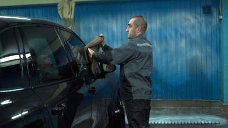 A Caucasian man works in a car wash service. A man in a worker's uniform is wiping his car with a rag.