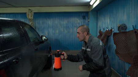 A Caucasian man works in a car wash service. A man in a workers uniform washes the car thoroughly by spraying it with a water pistol.