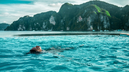 The girl swimming in the pool on the seashore overlooking mountains