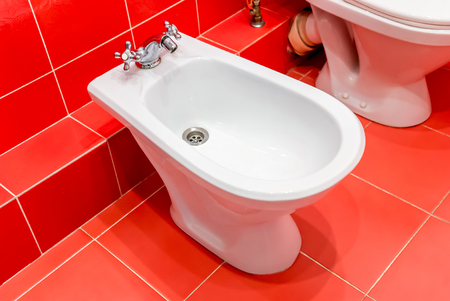 Photo close up white bidet in the red toilet room