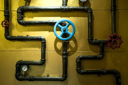 The photo of metal pipes for water supply with gate for opening and closing