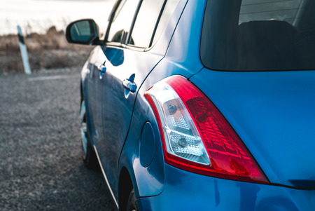 The photo of blue color of the car with reflections sideways