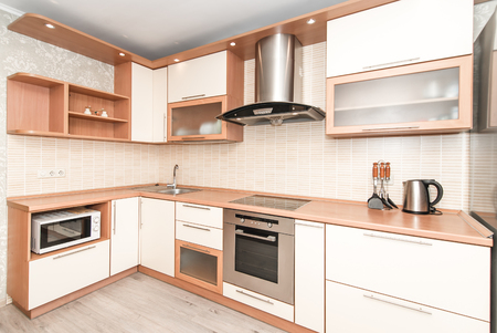 The photo of completely equipped light kitchen with household appliances Stock fotó