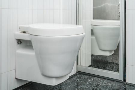 Das Foto der weißen Toilettenschüssel, die an einer Wand im Hoteltoilettenraum hängt Standard-Bild