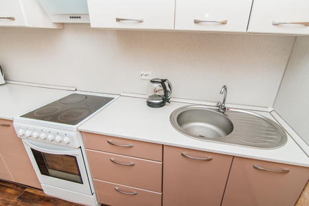 The photo of completely equipped light kitchen with household appliances Banco de Imagens
