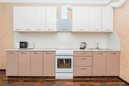 The photo of completely equipped light kitchen with household appliances