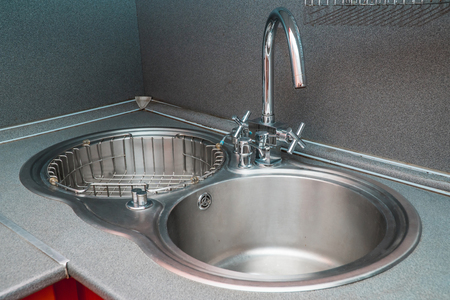 The photo of a white clean sink with the crane in the kitchen Banco de Imagens