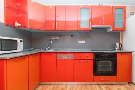 De foto van een volledig uitgeruste lichte keuken met huishoudelijke apparaten