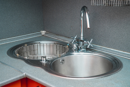 The photo of a white clean sink with the crane in the kitchen Stock Photo