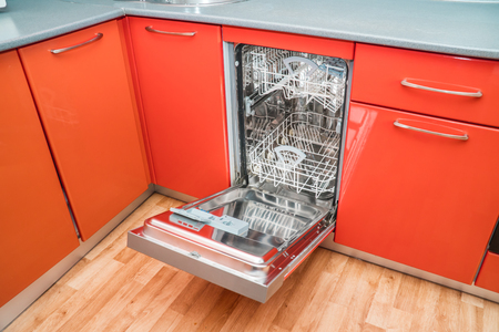 The photo of the built-in dishwasher in kitchen of orange color