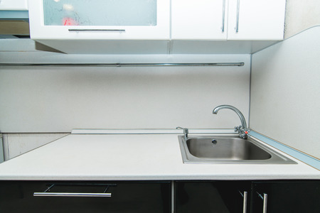 The photo of a white clean sink with the crane in the kitchen Stock fotó