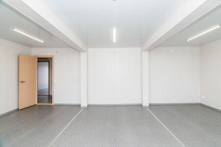 Das Foto des hellweißen leeren Büroraums mit heller Beleuchtung