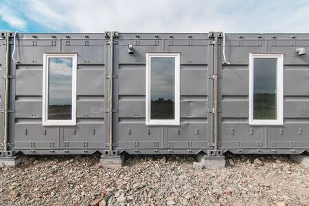 The photo of the house with windows and doors made of iron containers for cargo transportation