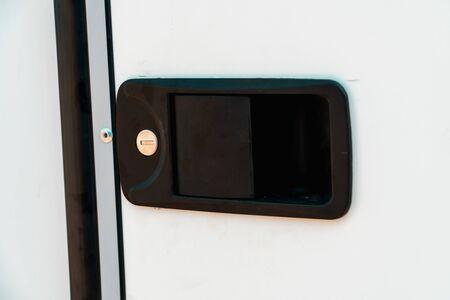 Photo of black door handle with keyhole on white door