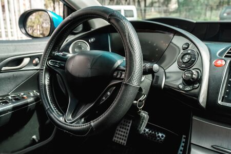 The bright photo of the dashboard in the car with black salon