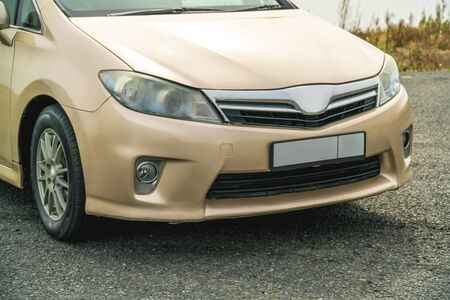 Photo of a car of gold color standing in a parking lot on the street Imagens