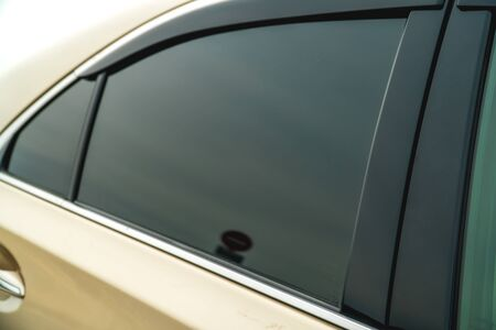 The photo of the darkened side glass on the gold car