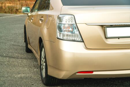 Photo of the back of a gold-coloured car close-up standing on the street