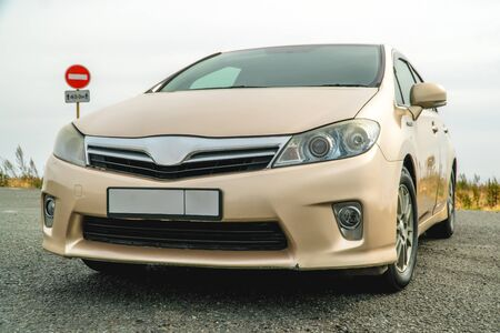 Photo of a car of gold color standing in a parking lot on the street 版權商用圖片
