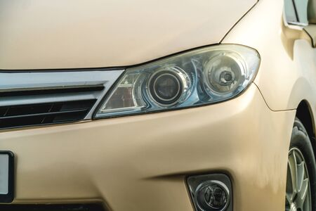 Photo of the front of a gold-coloured car close-up standing on the street Stok Fotoğraf