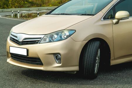 Photo of the front of a gold-coloured car close-up standing on the street Imagens