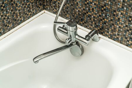 The photo of a white clean sink with the crane in the bathroom