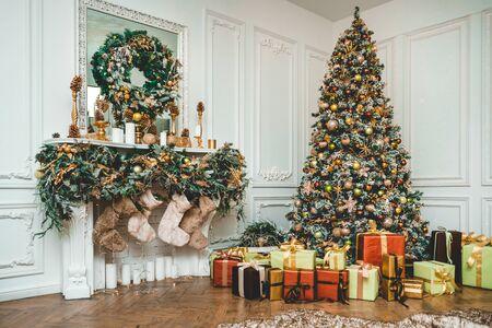 Silvester geschmückt mit Spielzeug grüner Baum mit Geschenken, die mit Kaminen stehen, auf denen Socken wiegen
