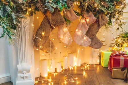 Photo of a New Year decorated fireplace with weighing socks for gifts