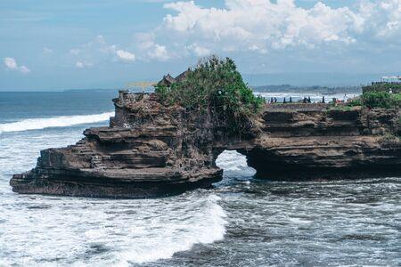 Photo of large waves crashing into large rocks on Nusa Penida island in Indonesia