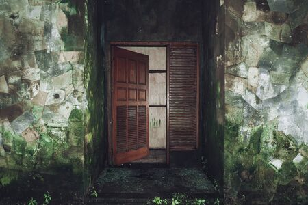 Dark photo of the room of an abandoned building with dirty walls