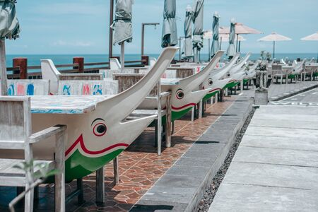Street cafe with umbrellas, chairs and tables in sea dolphin lead