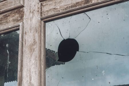 Photograph of an old wooden window on the street with broken glass with a hole