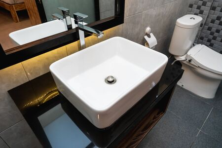 The photo of a ceramic sink and mirror in a bathroom Stock fotó