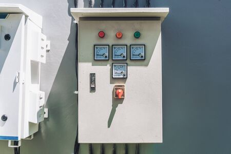 Photo of a large white electric panel with indicators of voltage and current of white color hanging on a wall on the street