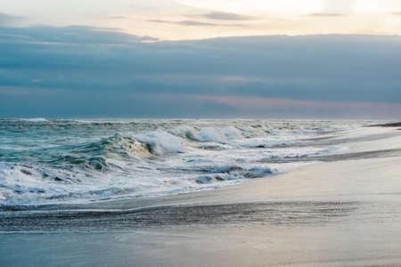 Photo of large waves crashing in sand beach rocks on bali island in Indonesia