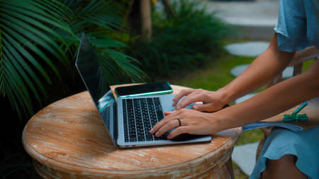 Photo of a young girl sitting at a wooden table and working behind a laptop in a green garden