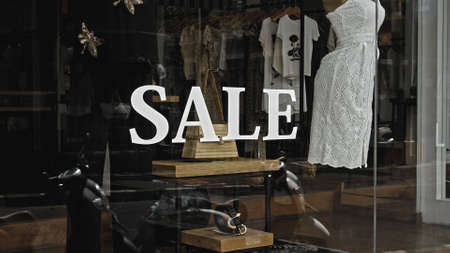 White text on the glass window of the store with the inscription sale