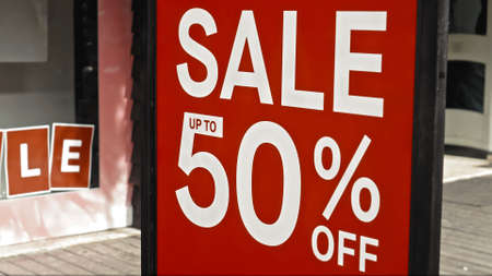 Red sign hanging on a glass window with the inscription sale up to 50% off