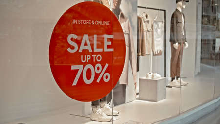 White text on the red sticker on the glass of window in the store with the inscription sale up to 70% off