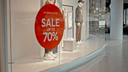 White text on the red sticker on the glass of window in the store with the inscription sale up to 70% off Reklamní fotografie