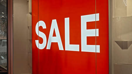 White text on the red board window of the store with the inscription sale