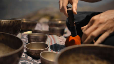 A young Asian guy playing Tibedt singing copper cups on a viewing mountain in nature