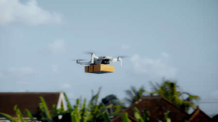 Photo of a flying on a sky delivery drone with holding a cardboard parcel 스톡 콘텐츠 - 163010719