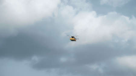Photo of a flying on a sky delivery drone with holding a cardboard parcel