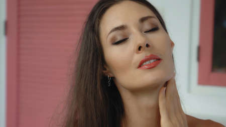 Young and beautiful European girl close-up touches the skin of the face with tender hands and fingers closing her eyes