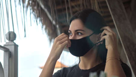 A young European brunette girl sits at a table in a public place and dresses a black protective mask on her face
