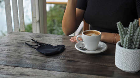 A young European girl sits at a table in a public place with a cup of coffee and nearby to her on a wooden table is a black protective mask 스톡 콘텐츠 - 163373581