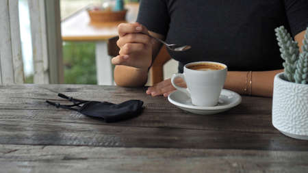 A young European girl sits at a table in a public place with a cup of coffee and nearby to her on a wooden table is a black protective mask